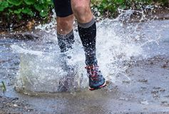 Man trail running in the mountains, crossing a creek. Man trail running in the mountain Royalty Free Stock Photo