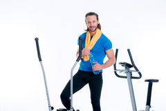 Man train with fitness machine and drinking water Stock Photo
