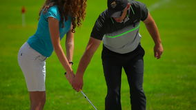 The man train a girl how to hit the ball in golf stock video