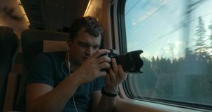 Man in train listening to music and making footage stock video footage