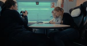 Making stock footage when mom with son playing on pad in train. Man in train shooting video of passing landscape while child with mom playing on digital tablet stock video