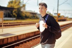 Man on train station, travel. Student in railway station. Smile freelance man. Boy with backpack waiting in a train station in sun stock photo