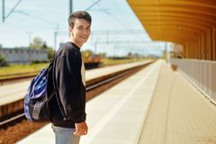 Man on train station, travel. Student in railway station. Smile freelance man. Boy with backpack waiting in a train station in sun royalty free stock photos