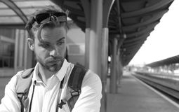 Man at the train station. Young man standing on platform at train station for travel. Travelling concept by train. Guy with thoughtful face waits for train stock photography