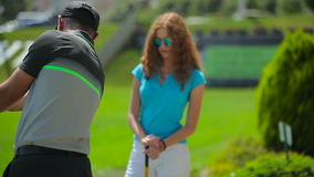 The man train the woman to hit the ball in golf stock video footage