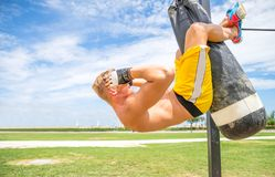 Man training abs on punching bag Stock Photos