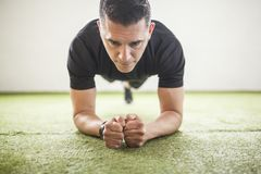Man training on artificial grass. Man training crunches over the artificial grass Royalty Free Stock Image