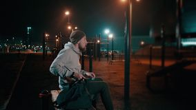 Man with training bag on athletic ground at night. Outdoor shot of a fitness guy packing his training bag and leaving sports ground late at night, lanterns lit stock video footage