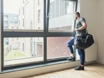 Man with training bag looking through a window Stock Photos