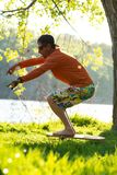 Man is training on the balance board on a green meadow. Bearded man is training on the balance board on a green meadow next to river on sunny evening. Back light Royalty Free Stock Images