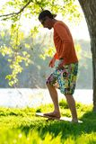 Man is training on the balance board on a green meadow. Bearded man is training on the balance board on a green meadow next to river on sunny evening. Back light Stock Photo