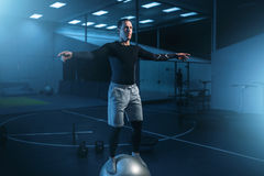Man on training, balance workout with bouncy ball. Strong man on training, balance workout with bouncy ball in gym. Active exercises in sport club Stock Photo