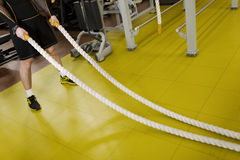 Man training with battle rope in fitness club Royalty Free Stock Image