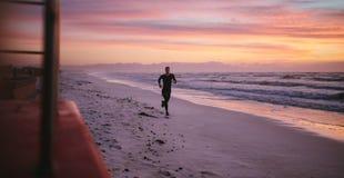 Man running on the beach in morning. Man training on the beach in morning. Healthy male athlete on morning run outdoors on seashore Stock Photos