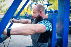 Man training on chest press equipment. Side view of man in sportswear training on chest press equipment in outdoor gym royalty free stock image