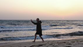 Man training Chinese martial art Taijiquan at sea beach, evening sky background. Man training Chinese martial art Taijiquan at sea beach on background evening stock video