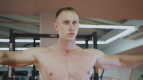 A man is training with dumbbells in the gym.  stock video footage