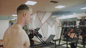 A man is training with dumbbells in the gym.  stock footage