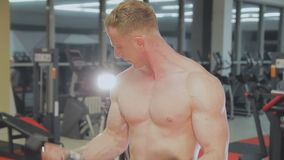 A man is training with dumbbells in the gym.  stock video
