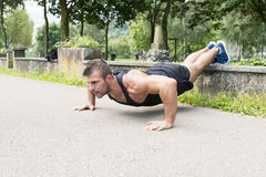 Man training and exercising doing push ups in the park. stock image