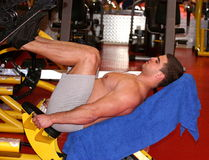 Man training in gym. Workout for legs using a machine Stock Photography