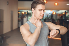 Man training in gym body health fit care. Male training in gym body workout checking pulse Royalty Free Stock Photography