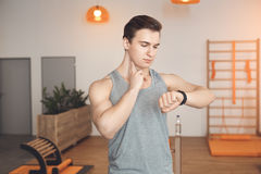 Man training in gym body health fit care. Male training in gym body workout checking pulse Stock Photography