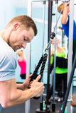 Man training in gym - fitness machine Royalty Free Stock Photo
