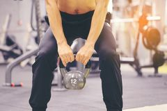Man training hand holding kettlebell for burn fat in the body in the sport gym, Healthy lifestyle and sport concept royalty free stock photography
