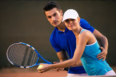 Man training her girlfriend how to play tennis Royalty Free Stock Image