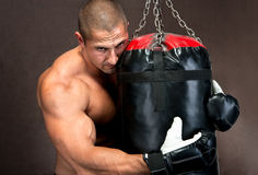 Man training kickboxing using black punching bag Royalty Free Stock Image