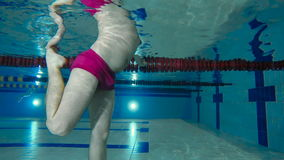 The man training the legs under water in the pool stock video footage