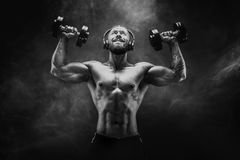 Man training muscles with dumbbells in studio on dark background Stock Image