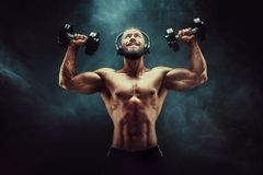 Man training muscles with dumbbells in studio on dark background with smoke. Royalty Free Stock Images