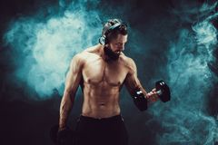 Man training muscles with dumbbells in studio on dark background with smoke. Royalty Free Stock Photos