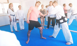 Man training new taekwondo holds with adults during class. Happy european men training new taekwondo holds with adults during class stock photos