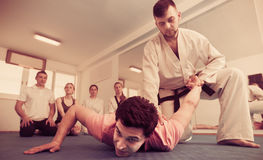 Man training new taekwondo holds with adults during class Stock Photography
