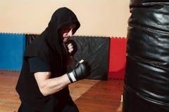 Man training with punching bag at gym Stock Photos
