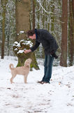 Man training puppy. Man training his puppy dog in a snow covered forest Stock Photo