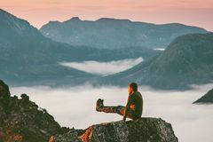 Man training sports on mountain cliff above clouds royalty free stock images