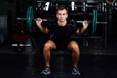 Man training squats with barbells over head. Handsome weightlifter training. Confident muscular man training squats with barbells over head. Closeup portrait of Royalty Free Stock Images