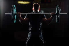 Man training squats with barbells over head. stock images