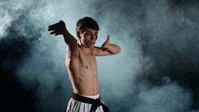 Man training taekwondo or karate with a naked. Karate man with a naked torso and a black belt. doing various exercises hands, smoke. close up. Slow motion stock footage