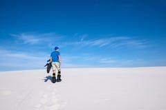 Man training to snowbord on the sand dune Stock Image