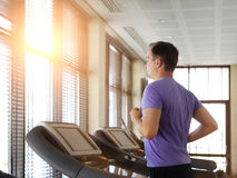 Man training on a treadmill in a sport centre. Young man training on a treadmill in a sport centre royalty free stock images