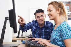 Man Training Woman On Computer In Office Royalty Free Stock Images
