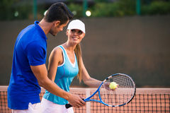 Man training woman how to play in tennis Royalty Free Stock Image