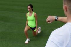 Man training woman. Selective focus on a stopwatch stock photos