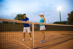 Man training woman to play tennis. Portrait of a men training women to play tennis outdoors Royalty Free Stock Image