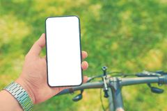Man trains on bike with smartphone royalty free stock photo